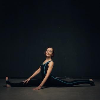 Übendes yoga der frau gegen eine dunkle strukturierte wand