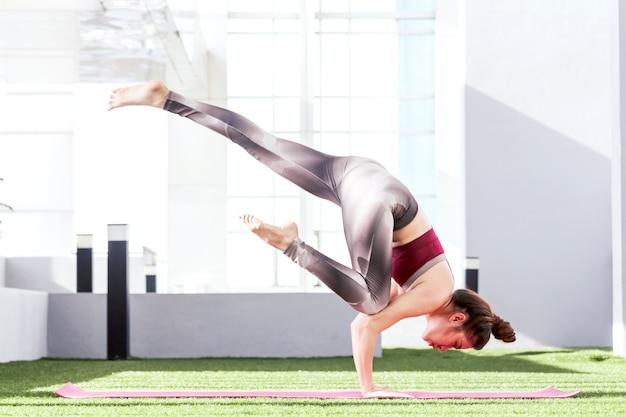 Übendes yoga der frau im park - gesunder lebensstil