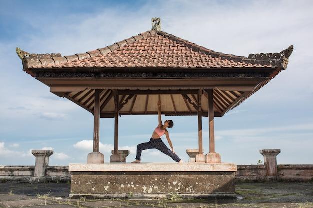 Übendes yoga der frau im traditionellen balinesse gazebo