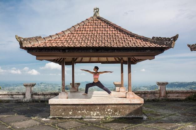 Übendes yoga der frau im traditionellen balinesse gazebo.