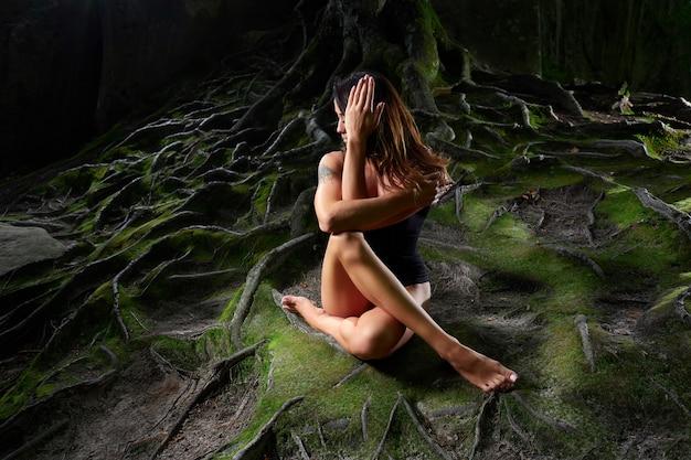 Übendes yoga der frau in einem mysteriösen dunklen wald, der nahe großem altem baum sitzt