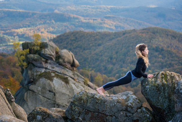 Übendes yoga der frau, tuend asana auf die oberseite des berges