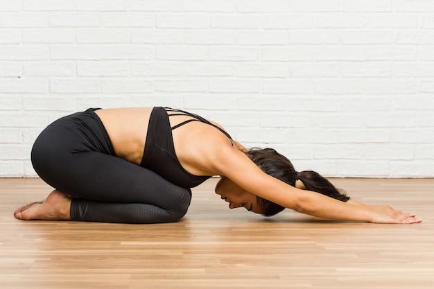 Übendes yoga der jungen arabischen sportlichen frau auf dem boden