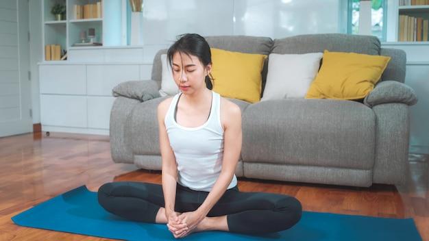Übendes yoga der jungen asiatin im wohnzimmer. attraktive schöne frau, die zu hause für gesundes ausarbeitet. lifestyle frau übungskonzept.