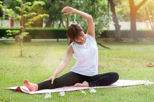 Übendes yoga der jungen asiatischen frau am abend im park