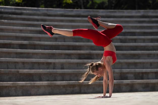 Übendes yoga der jungen attraktiven frau draußen. das mädchen führt einen handstand auf den kopf