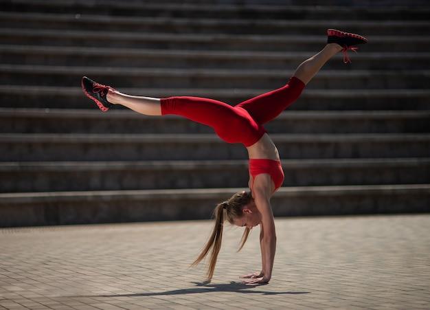 Übendes yoga der jungen attraktiven frau draußen. das mädchen führt einen handstand umgedreht durch