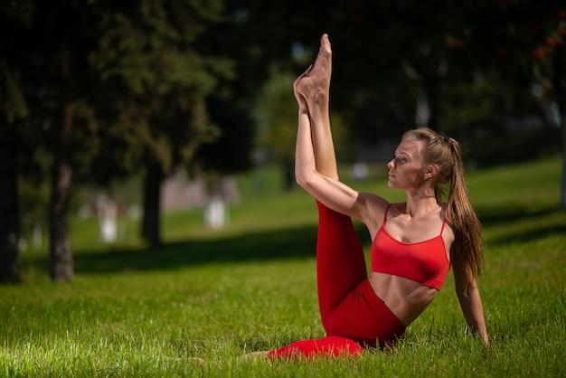 Übendes yoga der jungen attraktiven frau draußen. das mädchen führt verschiedene übungen auf dem gras durch