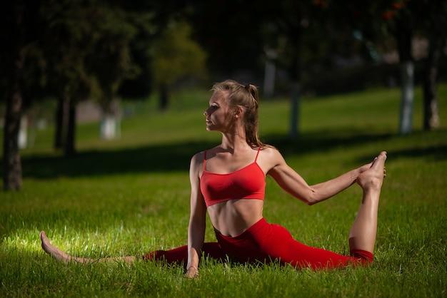 Übendes yoga der jungen attraktiven frau draußen.