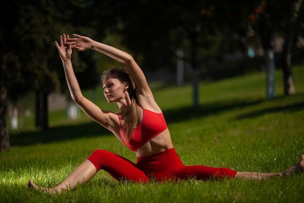Übendes yoga der jungen attraktiven frau draußen