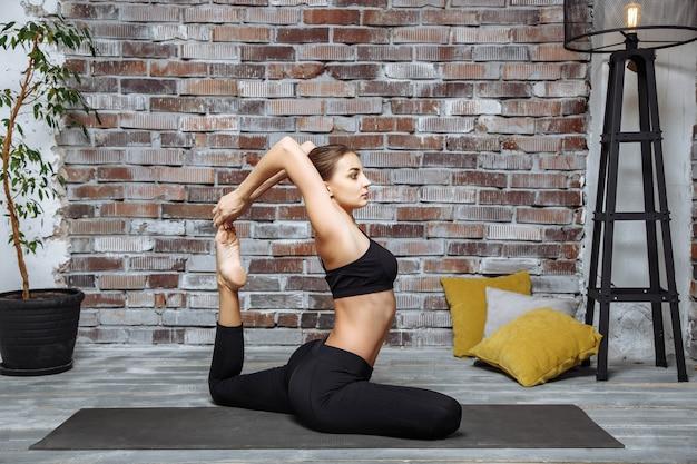 Übendes yoga der jungen attraktiven frau