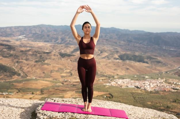 Übendes yoga der jungen frau auf die gebirgsoberseite