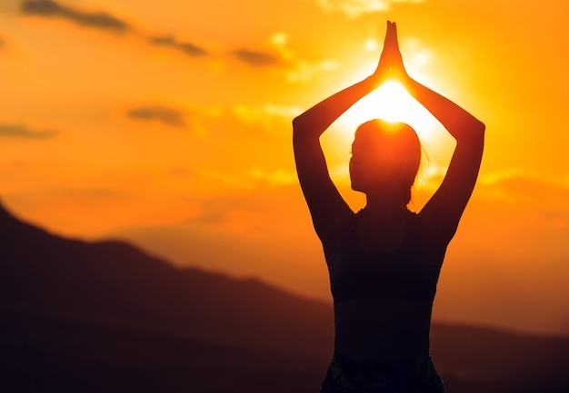 Übendes yoga der jungen frau bei sonnenuntergang im schönen gebirgsstandort.