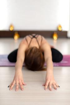 Übendes yoga der jungen frau, das in turnhalle ausdehnt