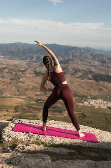 Übendes yoga der jungen frau der vorderansicht