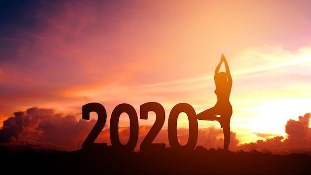Übendes yoga der jungen frau des schattenbildes auf 2020 neuem jahr