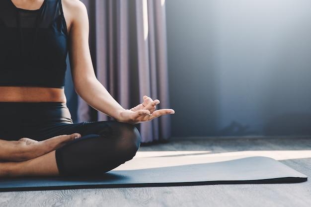 Übendes yoga der jungen frau in der klasse; das schöne mädchen, das ruhe glaubt und entspannen sich in der yogaklasse