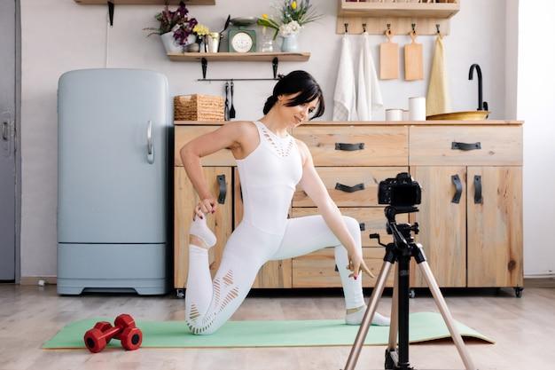 Übendes yoga der jungen frau und machen ein video mit ihrer kamera