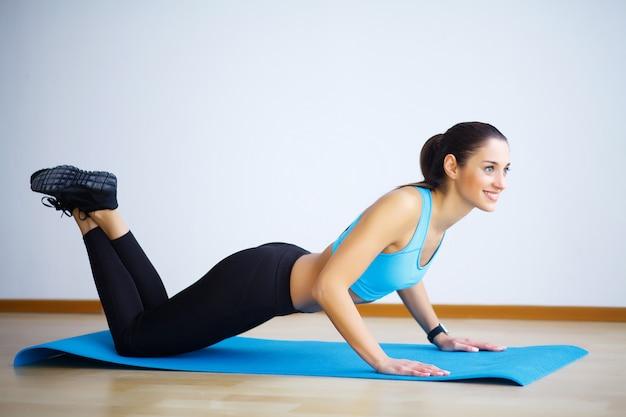 Übendes yoga der jungen frau, wilde sache tuend, drehen-die-hundübung, camatkarasana-haltung um und arbeiten aus und tragen sportkleidung, schwarze hosen und spitze, innenvoller länge, graue wand im yogastudio