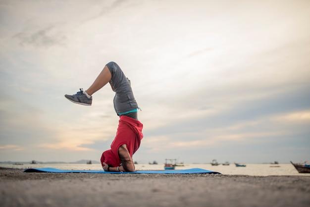 Übendes yoga der jungen gesunden frau auf dem strand bei sonnenaufgang