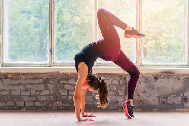 Übendes yoga der jungen kühlen attraktiven frau