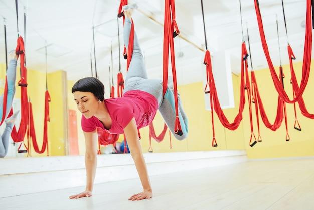Übendes yoga der jungen schönheit fliege mit einer hängematte