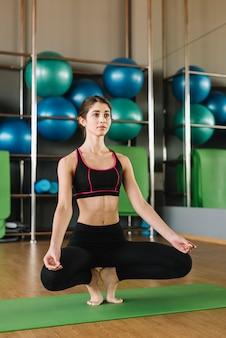 Übendes yoga der jungen sportlichen attraktiven frau in der turnhalle