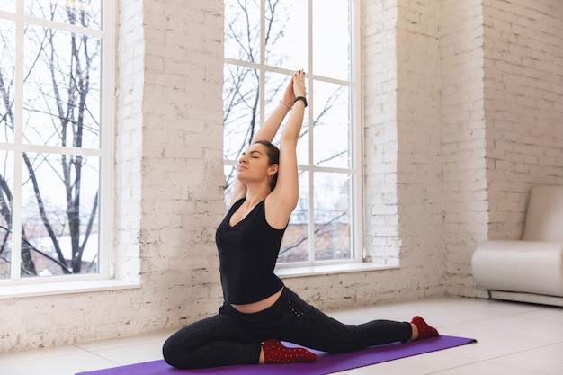 Übendes yoga der jungen sportlichen frau nahe dem fenster, eine mit beinen versehene taubenübung tuend