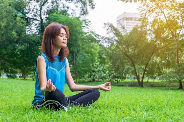 Übendes yoga der jungen und schönen asiatischen frau draußen im park mit grünem natur backgro