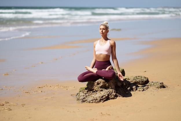 Übendes yoga der kaukasischen blondine im strand
