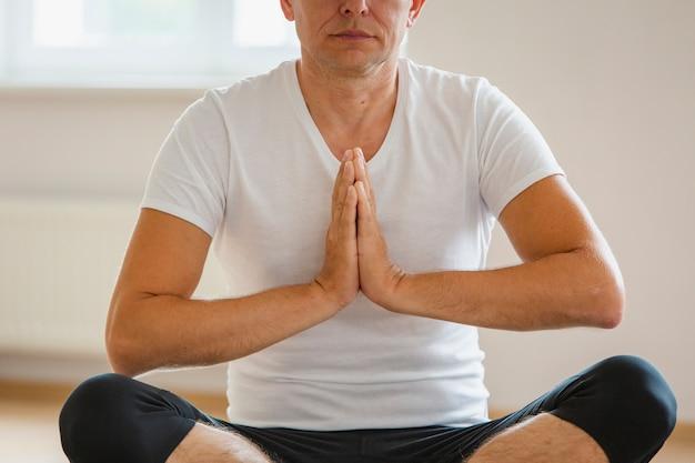 Übendes yoga der nahaufnahme erwachsener mann