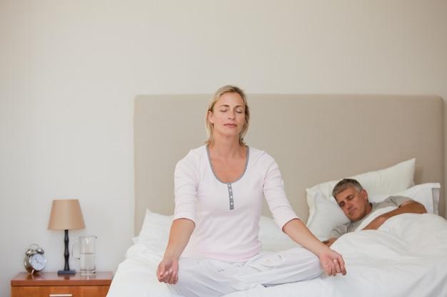 Übendes yoga der reizenden frau auf ihrem bett