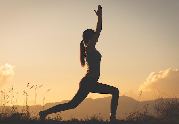 Übendes yoga der schattenbildfrau auf berg
