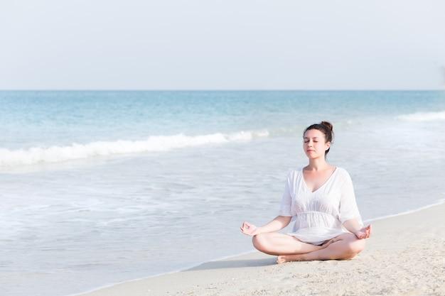 Übendes yoga der schwangeren frau der junge in meer