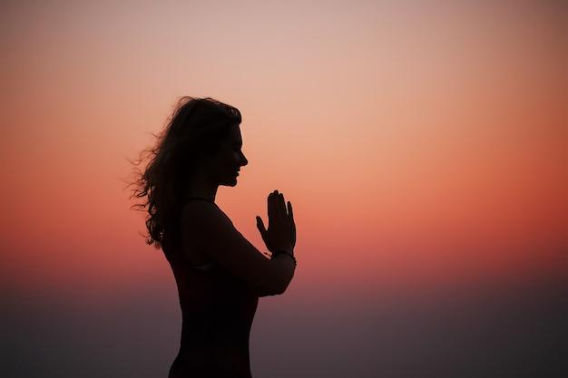 Übendes yoga der sportlichen frau im park bei sonnenuntergang