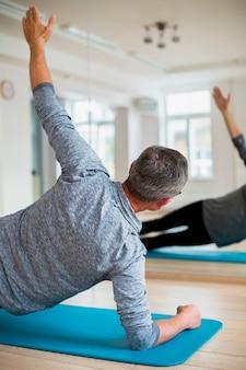Übendes yoga des älteren mannes der hinteren ansicht
