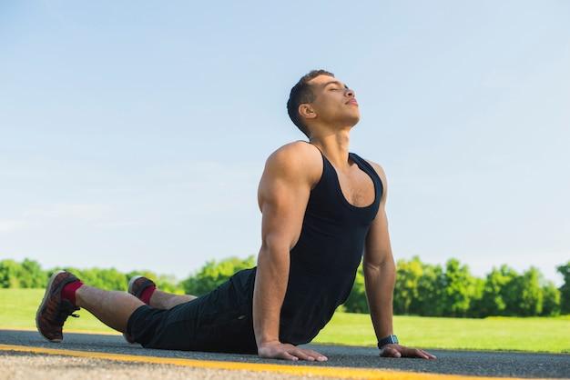 Übendes yoga des athletischen mannes im freien