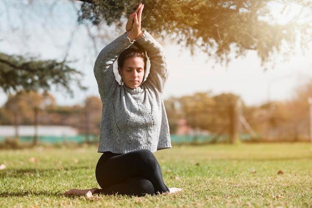 Übendes yoga des entspannten mädchens im freien