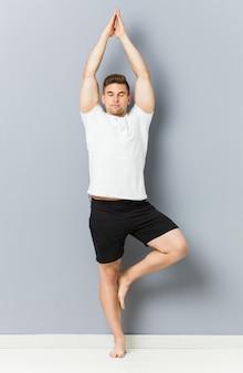 Übendes yoga des jungen kaukasischen mannes innen
