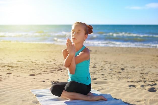Übendes yoga des mädchens am strand. getontes bild.