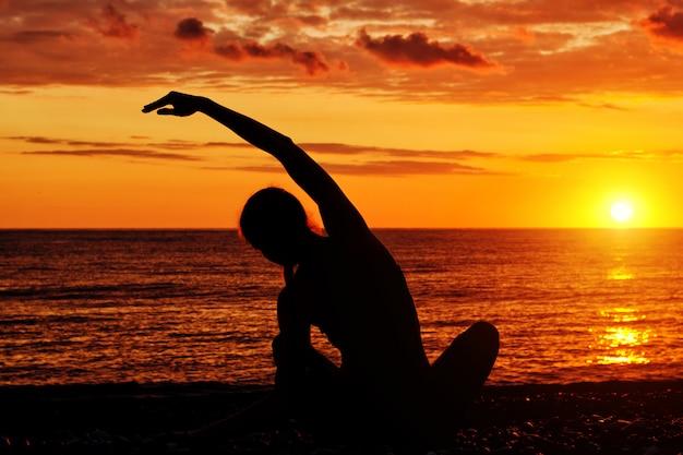 Übendes yoga des mädchens auf dem strand. blick von hinten, sonnenuntergang, silhouetten