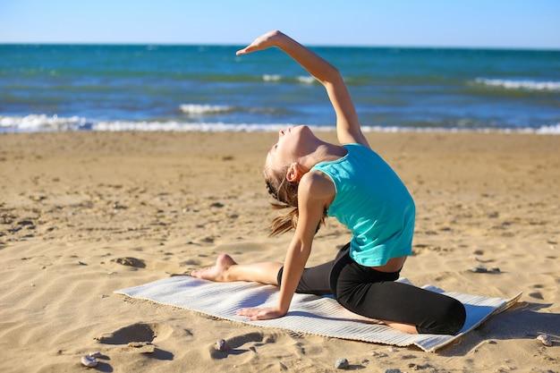 Übendes yoga des mädchens auf dem strand. Premium Fotos