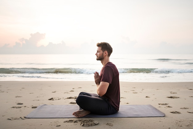 Übendes yoga des mannes auf dem strand