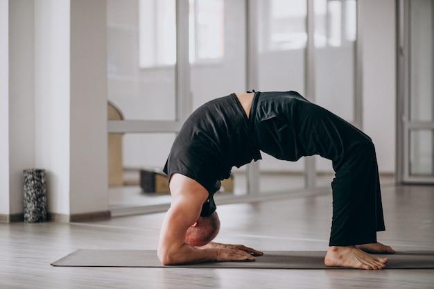Übendes yoga des mannes in der turnhalle