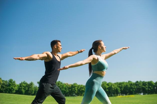 Übendes yoga des mannes und der frau im freien