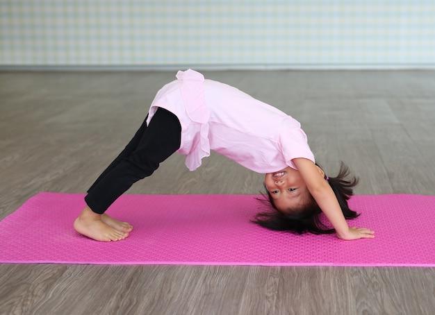 Übendes yoga des netten kleinkindmädchens und handeln der übung