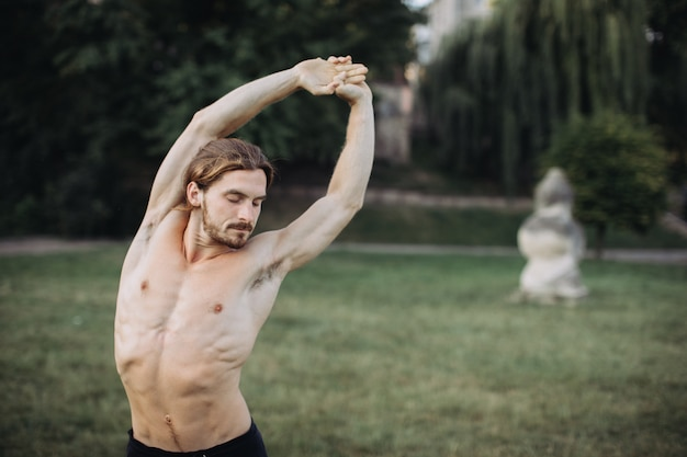 Übendes yoga des sportlichen mannes im freien