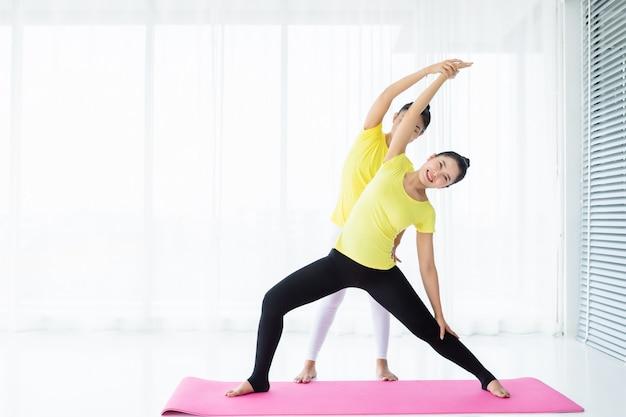 Übendes yoga des trainings mit zwei jungen asiatinnen im gelben kleid oder haltung mit einem trainer und einer praxis