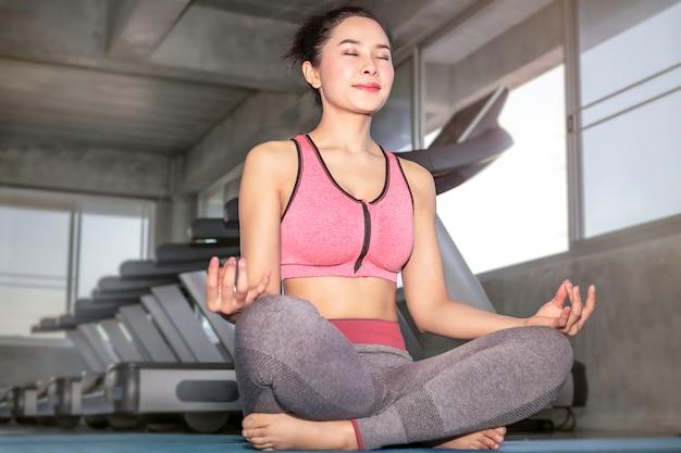 Übendes yoga junger asien-frau auf turnhalle. lotoshaltung auf meditationssitzung.