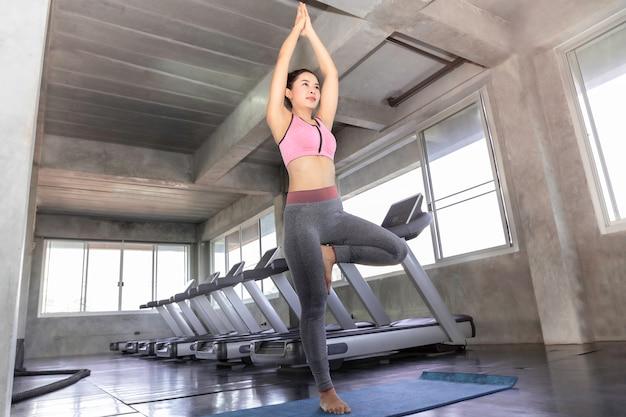 Übendes yoga junger asien-frau mit sportkleidungs-bh und -hosen an der eignungsturnhalle